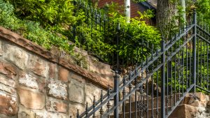 Pano frame Outdoor staircase with stone steps and black metal railing against a fence