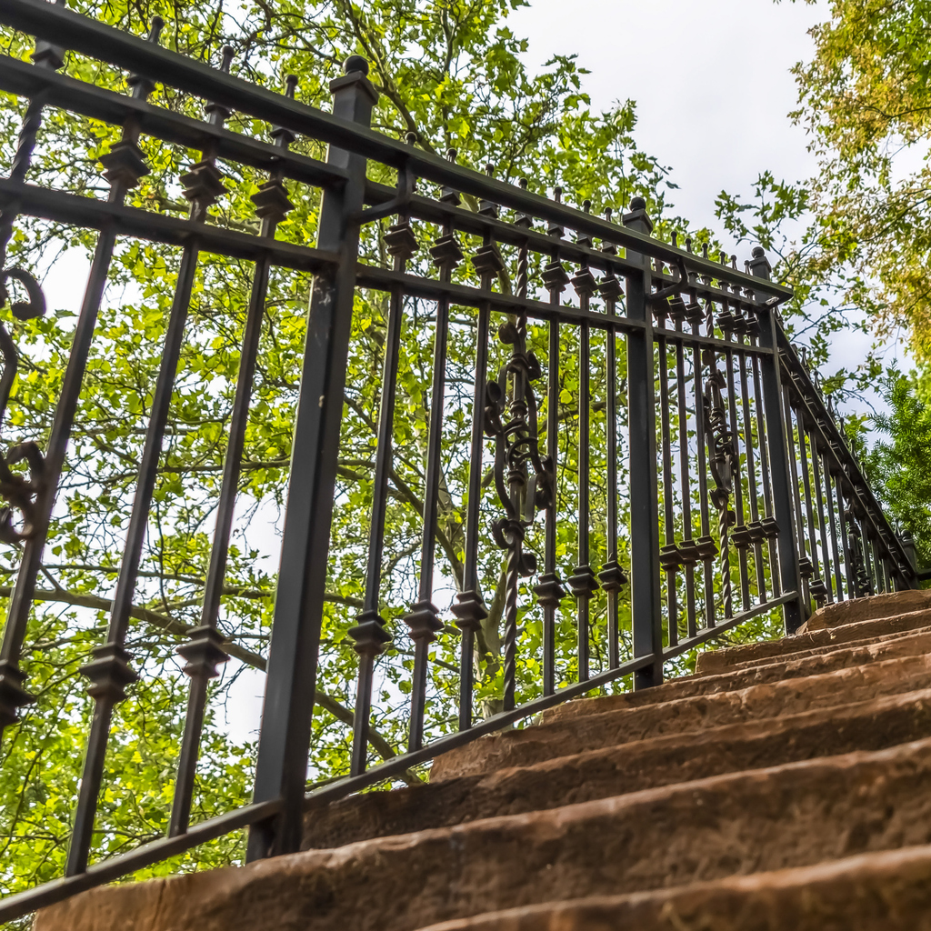 Square frame Close up of staircase with stone treads and metal railing against leaves and sky