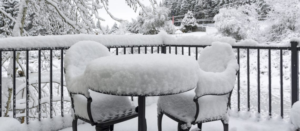 A snow covered deck, table and chairs. Overcast day causing a very monotone look. Small amount of colors showing.